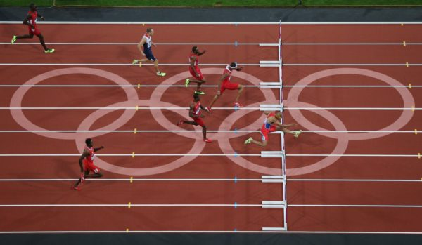 Olympic runners hurdling on a track